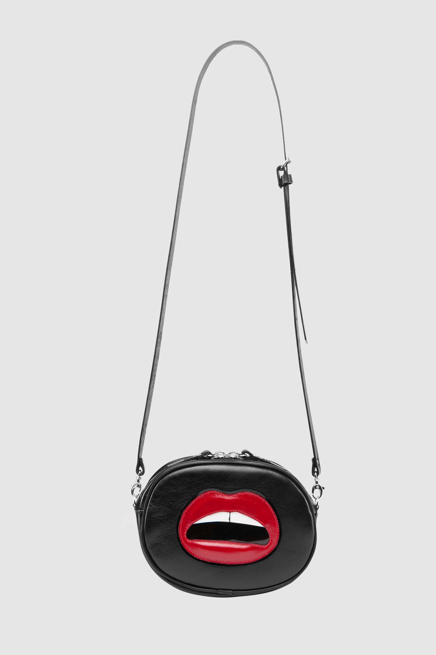 Сумка «Crazy chic»Овальная сумка из мягкой натуральной кожи на молнии с серебряной фурнитурой и цветной аппликацией. Внутреннее отделение на подкладке. Несмотря на небольшие размеры, сумка очень вместительная. Съемный регулируемый ремешок через плечо.&#13;<br>&#13;<br>Кожа: КРС.&#13;<br>&#13;<br>Размеры&#13;<br>Высота: 12,5 см&#13;<br>Длина: 16,6 см&#13;<br>Глубина: 5 см&#13;<br>Высота ремешка: max 120 - min 70 см<br><br>Цвет: Черный
