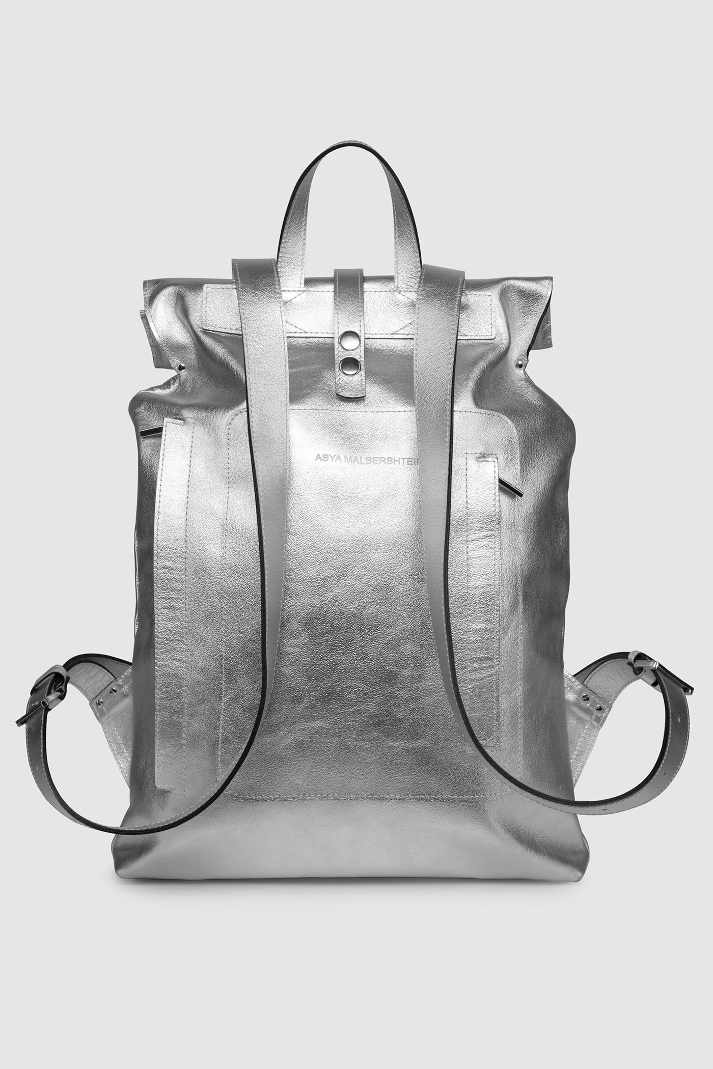 Рюкзак среднего размераГородской рюкзак прямоугольной формы из кожи&#13;<br>&#13;<br>&#13;<br>лямки на регуляторах&#13;<br>&#13;<br>тканевая подкладка&#13;<br>&#13;<br>закрывается на кнопки и хлястик&#13;<br>&#13;<br>внешний накладной карман на хлястике&#13;<br>&#13;<br>на задней поверхности рюкзака дополнительный доступ в основной отсек через молнию и потайной карман на молнии&#13;<br>&#13;<br>размеры: 44х33 см, ширина горла 26 см<br><br>Цвет: Серебро<br>Размер: one size